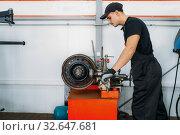 Repairman works with crumpled disc, tire service. Стоковое фото, фотограф Tryapitsyn Sergiy / Фотобанк Лори