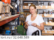 Купить «Woman holding shop list and choosing tools at shelves in build store», фото № 32648589, снято 20 сентября 2018 г. (c) Яков Филимонов / Фотобанк Лори