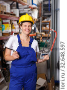 Woman in uniform and helmet standing near racks in build store holding saw. Стоковое фото, фотограф Яков Филимонов / Фотобанк Лори