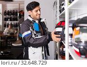 Man in moto jacket is choosing new helmet for motorbike in the store. Стоковое фото, фотограф Яков Филимонов / Фотобанк Лори