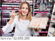 Купить «Young cheerful woman applying blush with makeup brush in cosmetics store», фото № 32650285, снято 19 октября 2019 г. (c) Яков Филимонов / Фотобанк Лори