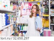 Купить «Cheerful woman holding two bottles of rinse aid», фото № 32650297, снято 19 октября 2019 г. (c) Яков Филимонов / Фотобанк Лори