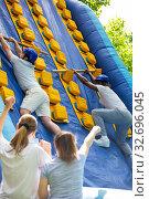 Men competing in climbing on inflatable slide. Стоковое фото, фотограф Яков Филимонов / Фотобанк Лори