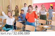 Купить «Happy students talking on phones», фото № 32696089, снято 29 марта 2020 г. (c) Яков Филимонов / Фотобанк Лори