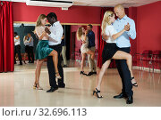 Купить «Portrait of positive adult pairs enjoying tango in modern dance hall», фото № 32696113, снято 4 октября 2018 г. (c) Яков Филимонов / Фотобанк Лори