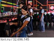 Купить «Positive friends looking laser guns and clothes», фото № 32696145, снято 23 августа 2018 г. (c) Яков Филимонов / Фотобанк Лори
