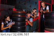 Купить «Smiling young friends playing laser tag game with colored laser guns near tires in labyrinth», фото № 32696161, снято 23 августа 2018 г. (c) Яков Филимонов / Фотобанк Лори