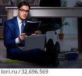 Купить «The businessman working overtime long hours late in office», фото № 32696569, снято 9 октября 2017 г. (c) Elnur / Фотобанк Лори
