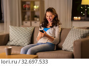 woman with smartphone at home. Стоковое фото, фотограф Syda Productions / Фотобанк Лори