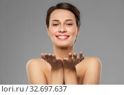 Купить «beautiful young woman holding something on palms», фото № 32697637, снято 30 ноября 2019 г. (c) Syda Productions / Фотобанк Лори