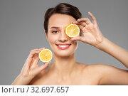 beautiful woman making eye mask of lemon slices. Стоковое фото, фотограф Syda Productions / Фотобанк Лори