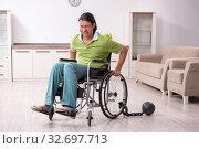 Купить «Young male invalid in wheel-chair suffering at home», фото № 32697713, снято 23 июля 2019 г. (c) Elnur / Фотобанк Лори