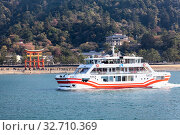 Купить «Ferryboat of JR company comes from the island of Miyajima (Itsukushima) in Hiroshima gulf. View from the Miyajimaguchi city. Great Torii ferry service. Japan», фото № 32710369, снято 13 апреля 2013 г. (c) Кекяляйнен Андрей / Фотобанк Лори