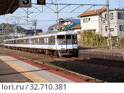 Electric train by West Japan Railway Company (JR West) is on Sanyo Main Line. View from Miyajimaguchi Station, Hatsukaichi, Hiroshima (2013 год). Редакционное фото, фотограф Кекяляйнен Андрей / Фотобанк Лори