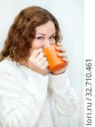 Cheerful woman drinking tea from orange mug, dressed white knitted pullover, curly hair. Стоковое фото, фотограф Кекяляйнен Андрей / Фотобанк Лори