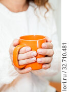 Big orange tea mug in female hands on white knitted sweater. Стоковое фото, фотограф Кекяляйнен Андрей / Фотобанк Лори