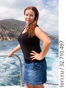 Curly hair woman dressing, jeans skirt and black t-shirt posing in deck of driving powerboat. Стоковое фото, фотограф Кекяляйнен Андрей / Фотобанк Лори
