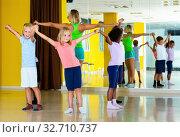 Group of tweens exercising folk dance, forming circle with femal. Стоковое фото, фотограф Яков Филимонов / Фотобанк Лори