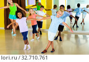 Group of children practicing vigorous jive movements in dance class with female coach. Стоковое фото, фотограф Яков Филимонов / Фотобанк Лори