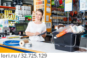 Купить «Young female seller standing at the counter in household tools store», фото № 32725129, снято 17 мая 2018 г. (c) Яков Филимонов / Фотобанк Лори