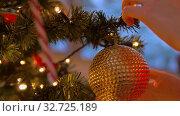 Купить «woman decorating christmas tree with ball», видеоролик № 32725189, снято 16 декабря 2019 г. (c) Syda Productions / Фотобанк Лори