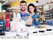 Купить «Young vigorous couple demonstrating tools for house renovating in paint store», фото № 32725193, снято 9 марта 2017 г. (c) Яков Филимонов / Фотобанк Лори
