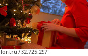 Купить «woman taking gift box from under christmas tree», видеоролик № 32725297, снято 16 декабря 2019 г. (c) Syda Productions / Фотобанк Лори