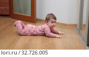 Caucasian baby lying on floor in domestic room, creeper in crawlers learning to crawl. Стоковое видео, видеограф Кекяляйнен Андрей / Фотобанк Лори
