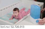 Купить «Mother brings her baby in crib and turns on the humidifier for infant comfort sleeping», видеоролик № 32726013, снято 9 декабря 2019 г. (c) Кекяляйнен Андрей / Фотобанк Лори