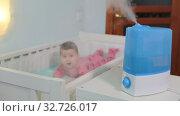Радостный малыш в кроватке на фоне работающего увлажнителя воздуха. Стоковое видео, видеограф Кекяляйнен Андрей / Фотобанк Лори
