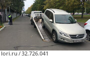 Купить «Police tows suv for parking violations. Illegal parking on pedestrian pathway. Tow truck works under Russian policeman direction», видеоролик № 32726041, снято 2 октября 2019 г. (c) Кекяляйнен Андрей / Фотобанк Лори