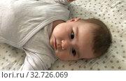Купить «Newborn baby lying back in bed, close up portrait, head and shoulders. Two month infant», видеоролик № 32726069, снято 2 октября 2019 г. (c) Кекяляйнен Андрей / Фотобанк Лори
