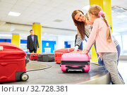 Mutter und Kinder als Passagiere suchen ihre Koffer am Gepäckband im Flughafen Terminal. Стоковое фото, фотограф Zoonar.com/Robert Kneschke / age Fotostock / Фотобанк Лори
