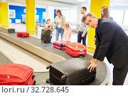 Geschäftsmann und andere Passagiere holen ihr Gepäck ab vom Gepäckband im Flughafen. Стоковое фото, фотограф Zoonar.com/Robert Kneschke / age Fotostock / Фотобанк Лори