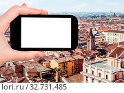 Travel concept - tourist photographs Verona city skyline from tower Torre dei Lamberti in spring on smartphone with cut out screen for advertising logo. Стоковое фото, фотограф Zoonar.com/Valery Voennyy / easy Fotostock / Фотобанк Лори
