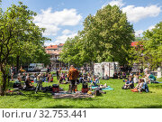 Street musician gives concert on a meadow on 1 May in Schlesische Strasse in Berlin-Kreuzberg (2018 год). Редакционное фото, агентство Caro Photoagency / Фотобанк Лори
