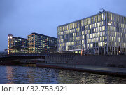 Berlin, Germany, view of the central station (left) and the office building of pwc in the evening from the Spree (2017 год). Редакционное фото, агентство Caro Photoagency / Фотобанк Лори