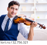 Купить «Young musician man practicing playing violin at home», фото № 32756321, снято 15 августа 2017 г. (c) Elnur / Фотобанк Лори