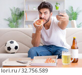 Купить «Man eating pizza having a takeaway at home relaxing resting», фото № 32756589, снято 18 июля 2017 г. (c) Elnur / Фотобанк Лори