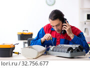Young repairman repairing air-conditioner at warranty center. Стоковое фото, фотограф Elnur / Фотобанк Лори