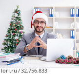 Купить «Young businessman celebrating christmas in the office», фото № 32756833, снято 22 июля 2017 г. (c) Elnur / Фотобанк Лори