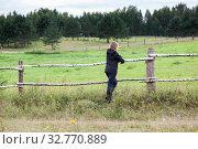 Mature grey-haired female farmer leaning on a paddock fence watching the farm field in the distance. Стоковое фото, фотограф Кекяляйнен Андрей / Фотобанк Лори