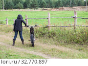 Rear view at female dressed black raincoat with hood on head standing with dirt motorcycle on countryside road in village, copyspace. Стоковое фото, фотограф Кекяляйнен Андрей / Фотобанк Лори