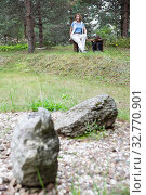 Купить «Mature woman sitting on wooden bench with pensive mood, stone garden with pebbles on foreground, evergreen forest», фото № 32770901, снято 11 августа 2019 г. (c) Кекяляйнен Андрей / Фотобанк Лори