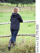 Rear view of woman wearing black clothes standing her back to camera, keeping hands on fence, came to rural field to relax. Стоковое фото, фотограф Кекяляйнен Андрей / Фотобанк Лори