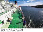 Купить «Passengers are on upper side deck of cruise ferry. It is cruise liner of Viking line Finnish shipping company. Trip from Helsinki to Stockholm», фото № 32770921, снято 2 июля 2018 г. (c) Кекяляйнен Андрей / Фотобанк Лори