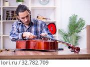 Купить «Young handsome repairman repairing cello», фото № 32782709, снято 4 апреля 2019 г. (c) Elnur / Фотобанк Лори