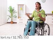 Купить «Young male invalid in wheel-chair suffering at home», фото № 32783153, снято 23 июля 2019 г. (c) Elnur / Фотобанк Лори