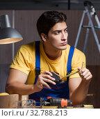 Купить «Worker working in repair workshop in woodworking concept», фото № 32788213, снято 11 августа 2017 г. (c) Elnur / Фотобанк Лори