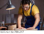 Купить «Worker working in repair workshop in woodworking concept», фото № 32788217, снято 11 августа 2017 г. (c) Elnur / Фотобанк Лори